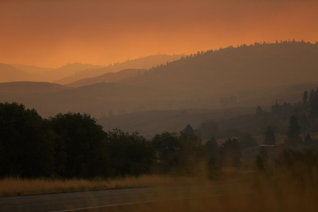 The sun barely illuminates the land under a thick fog of red smoke as seen from Highway 97 just south of Okanogan Friday August 21, 2015.